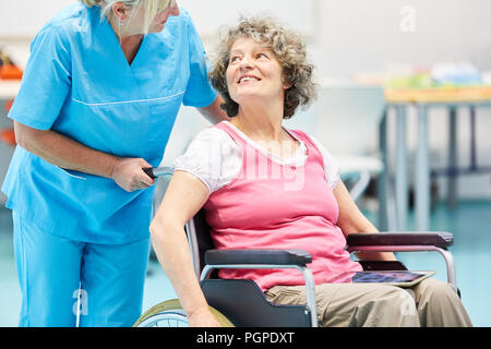 Nurse caring for senior woman in wheelchair after stroke in rehab clinic - Stock Photo