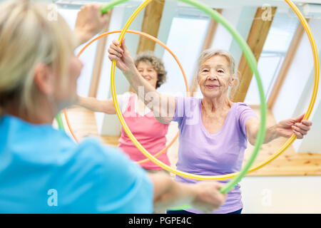 Seniors do fitness training with the tire in the physiotherapy - Stock Photo