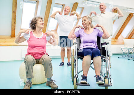 Seniors do exercises for the healthy back in the physiotherapy - Stock Photo