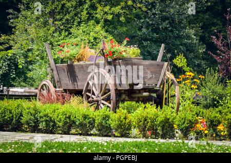 Beautiful natural summer scenery. Muted car with flowers in the garden. - Stock Photo