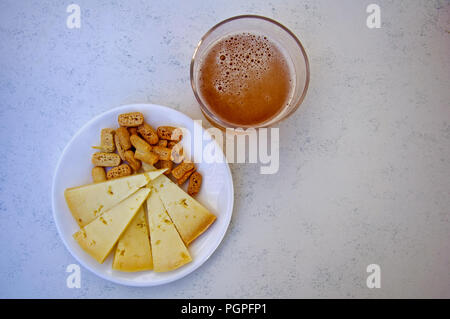 One glass of beer, cheese and crackers, center, view from above - Stock Photo