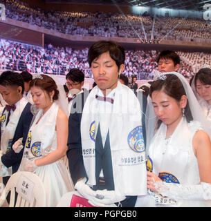 Seoul, South Korea. 27th Aug 2018. Mass wedding ceremony of the Unification Church, Aug 27, 2018 : Couples from Japan pray during a mass wedding ceremony of the Unification Church at the CheongShim Peace World Center in Gapyeong, about 60 km (37 miles) northeast of Seoul, South Korea. Four thousand newlywed couples from around the world participated in the mass wedding on Monday, which was organized by Hak Ja Han Moon, wife of the late Reverend Sun Myung Moon. Credit: Aflo Co. Ltd./Alamy Live News - Stock Photo