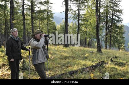 Russian President Vladimir Putin looks for wildlife during a hike with Federal Security Service Director Alexander Bortnikov at the Sayano-Shushensky Nature Reserve August 27, 2018 in the Siberian Tyva region of Russia. - Stock Photo