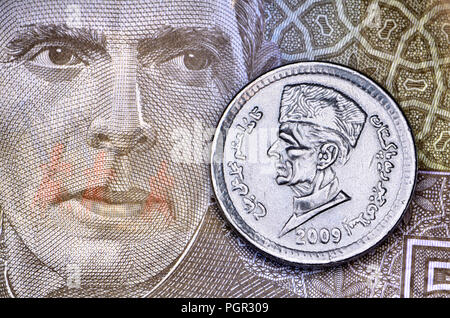 Pakistan 1 Rupee coin (2009) on a 5 Rupee banknote (2009), both showing the head of Muhammad Ali Jinnah (1876-1948) founder of Pakistan - Stock Photo