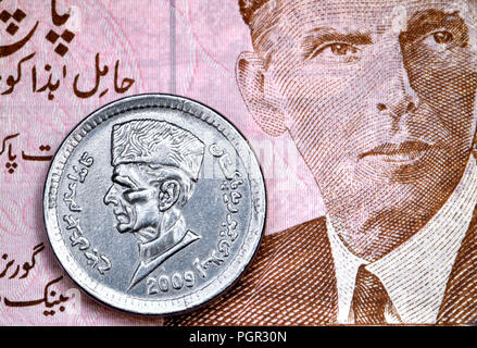Pakistan 1 Rupee coin (2009) on a 5 Rupee banknote, both showing the head of Muhammad Ali Jinnah (1876-1948) founder of Pakistan - Stock Photo