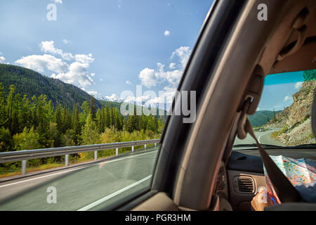 Woman inside the car driving and show map  on the country roadway between fields with brown grass and snowy mountains . Sun is shining. Shoot from the - Stock Photo