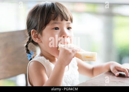 Cute Asian child eating butter toast at cafe. Outdoor family lifestyle with natural light. - Stock Photo