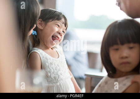 Candid shoot of people in cafeteria. Little girl with various face expression. Asian family outdoor lifestyle with natural light. - Stock Photo