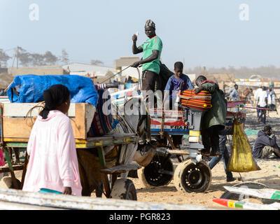 KAYAR, SENEGAL - APR 27, 2017: Unidentified Senegalese woman in pink shirt walks on the coast of the Atlantic Ocean. Many Kayar people work in port - Stock Photo