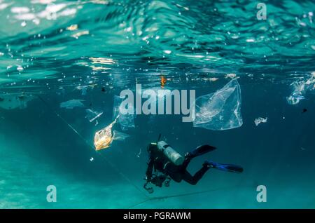Diver swims through plastic pollution underwater in Egypt - Stock Photo