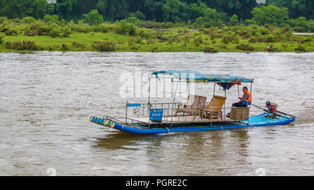 XINGPING, CHINA - MAY 11, 2018: The man on a raft crosses the Li River known as well as Lijiang River - Stock Photo
