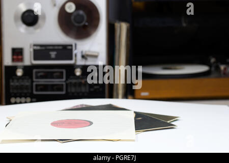 Vinyl record with copy space in front of a collection albums dummy titles. Reel Tape Recorder - Stock Photo