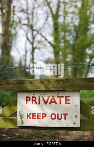 'Private Keep Out' sign on a gate in a woodland. - Stock Photo