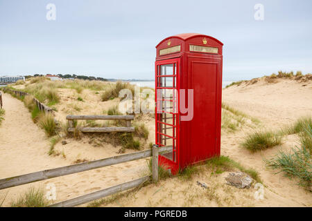 A bright red telephone box on the sand dunes at South Haven Point in Dorset at the end of the 630 mile South West Coast Path in England, UK. - Stock Photo
