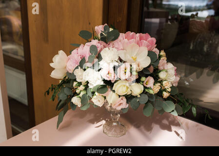 Composition from flowers - decoration of a table for guests. White candles in big glass vases - Stock Photo