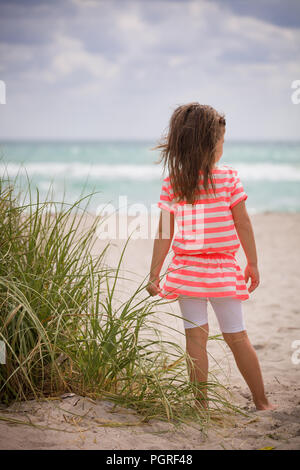Little adorable kid girl in striped dress standing on the sandy beach and looking at the ocean. Sea vacations. Child dreaming. Outdoors. Back view. - Stock Photo