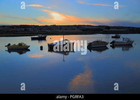 Boats on the river Axe estuary at sunset - Stock Photo