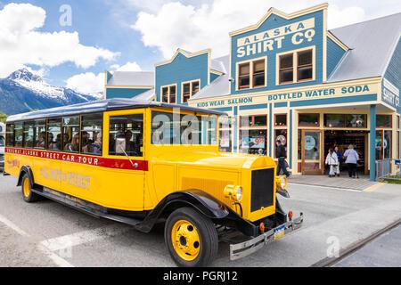 The Skagway Alaska Street Car Tour bus passing the Alaska Shirt Co. in Skagway, Alaska USA - Stock Photo