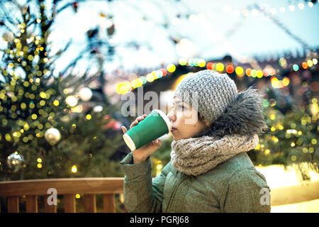 Beautiful young girl with a mug of hot drink at the Christmas market in Moscow.