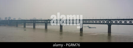 Panorama of old Wuhan Yangtze Great Bridge a truss double-deck road and rail bridge across the Yangtze River in Wuhan China on high peak pollution day - Stock Photo