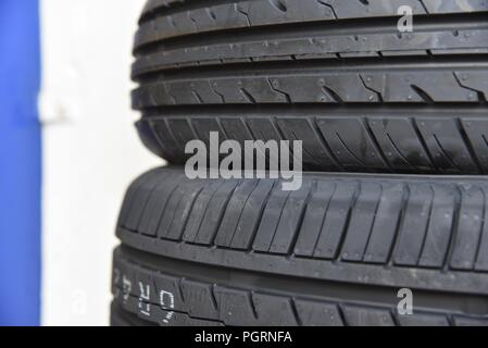 Tyre/tire fitting: a close up of new tyres stacked outside a workshop - Stock Photo