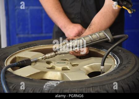 Tyre/tire fitting: a newly fitted tyre being inflated for the first time - Stock Photo