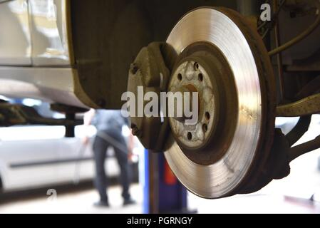 Tyre/tire fitting: a vehicle raised on a ramp and a wheel removed exposing the disc brake and caliper - Stock Photo