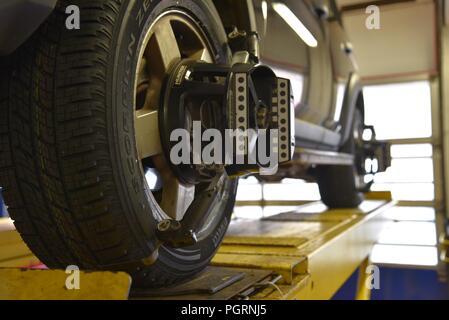 Tyre/tire fitting: a vehicle raised on a ramp and undergoing a wheel alignment test - Stock Photo