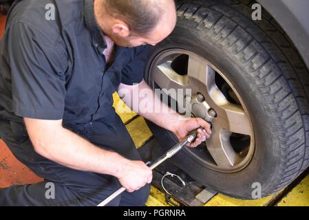Tyre/tire fitting: a tyre fitter removing wheel nuts in order to remove the wheel - Stock Photo