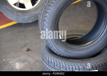 Tyre/tire fitting: new tyres at the ready for change-over - Stock Photo