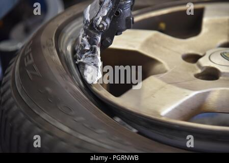 Tyre/tire fitting: a worn tyre being removed on a tyre changer - Stock Photo