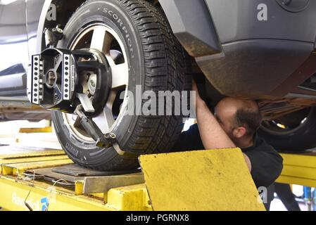 Tyre/tire fitting: a mechanic on the underside of a vehicle adjusting the tie-rod to align the wheel correctly - Stock Photo