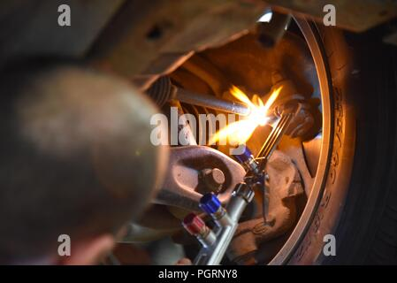 Tyre/tire fitting: a mechanic using an oxyacetylene torch to aid adjustment of a tie-rod - Stock Photo