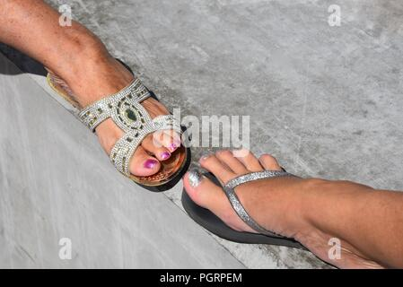 Footwear: two female feet toe-to-toe, one foot in a diamanté sandle the other in a glitter flip-flop