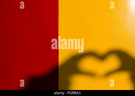 Silhouette of heart-shape hand on the bright yellow and red background. - Stock Photo