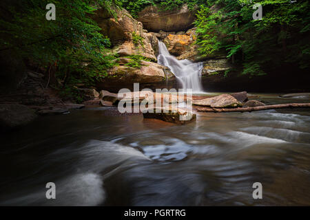 Water spills out of the sandstone cliffs, cradled by rocks, at Cedar Falls in Hocking Hills State Park, Ohio. - Stock Photo