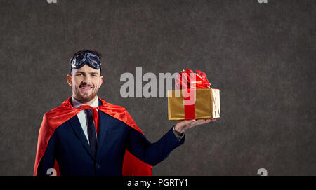 A man in a superhero costume with a gift box. - Stock Photo