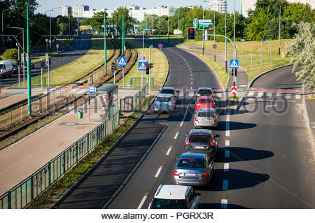 Rows of cars waiting in front of red traffic lights on a main road in Poznan, Poland - Stock Photo
