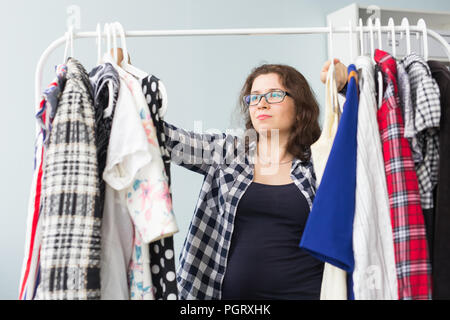 Beauty, fashion and people concept - Beautiful serious woman in black glasses chooses dresses - Stock Photo