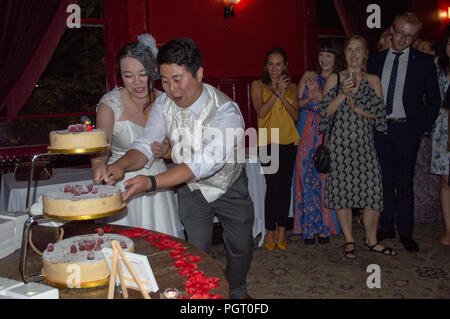 A bride and groom cutting their wedding cake - Stock Photo