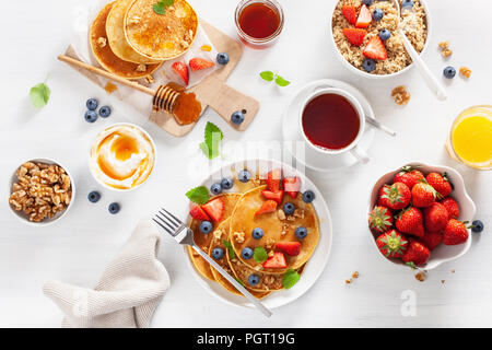 pancakes with blueberry strawberry honey and quinoa for breakfast - Stock Photo