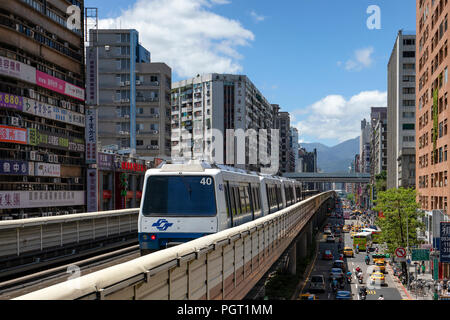 A train on the Taipei lightrail metro network leaves the Zhongxiao-Fuxing Station. - Stock Photo