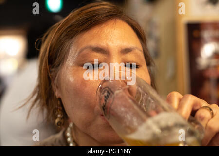 Mature Taiwanese/Chinese woman drinking beer in a restaurant - Stock Photo