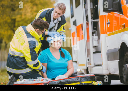 Emergency medics dressing head wound of injured woman - Stock Photo