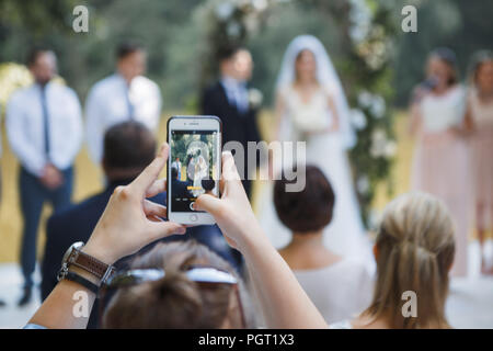 guest at the wedding ceremony takes pictures on the phone of the newlyweds - Stock Photo