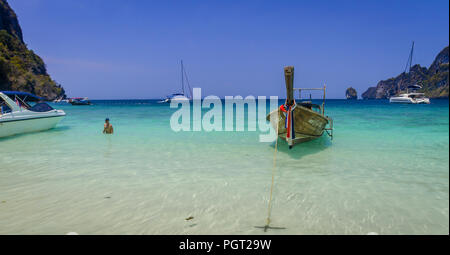 Long Boat off the coast of a Phi Phi  Island in Thailand. Beautiful colors and a man wading close to shore. - Stock Photo