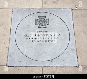 Plaque at foot of Manchester England war memorial showing Victoria Cross awarded Private George Stringer Manchester Regiment 8th March 1916 - Stock Photo