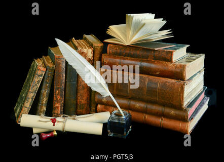 Still life with a letter, a pen and old books isolated on a black background - Stock Photo