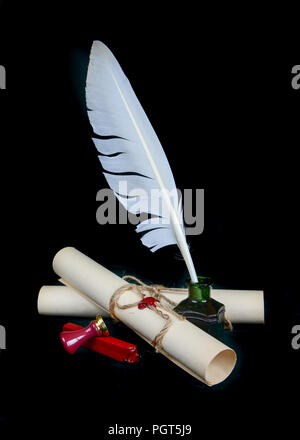 White feather in the inkwell, sealing wax, signet and two paper scroll isolated on black background - Stock Photo