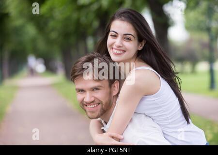 Portrait of smiling young girlfriend piggyback millennial boyfri - Stock Photo